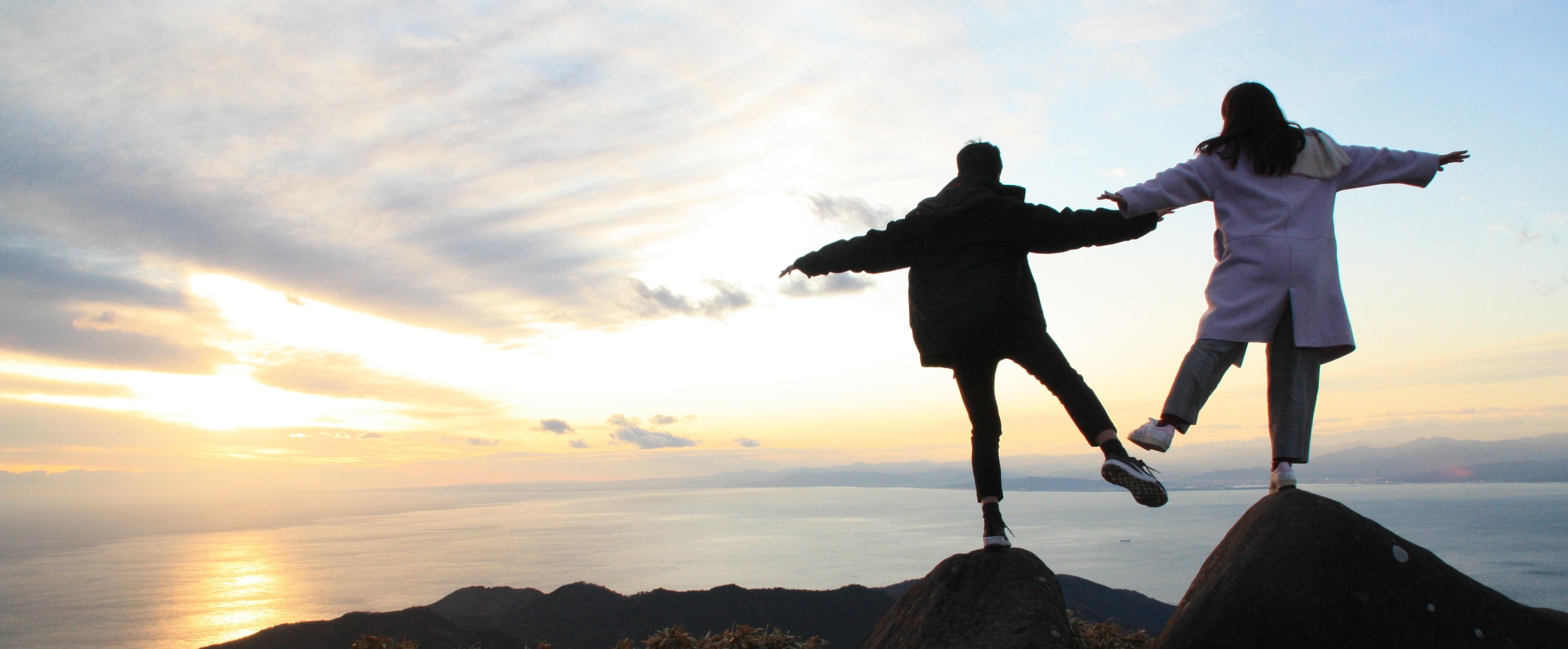 Meine Freundin und ich balancieren jeweils auf einem Stein und schauen den Sonnenuntergang über dem Meereshorizont an..