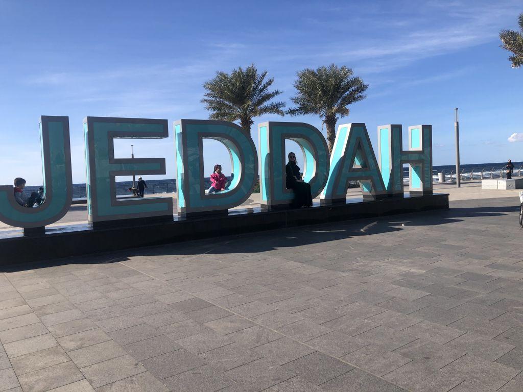"""Studentin Inga sitzt auf dem großen """"Jeddah""""-Zeichen"""