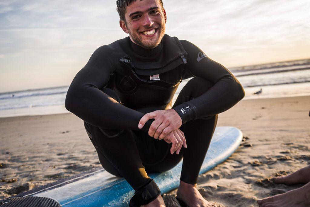 Ich mit Surfbrett am Strand.