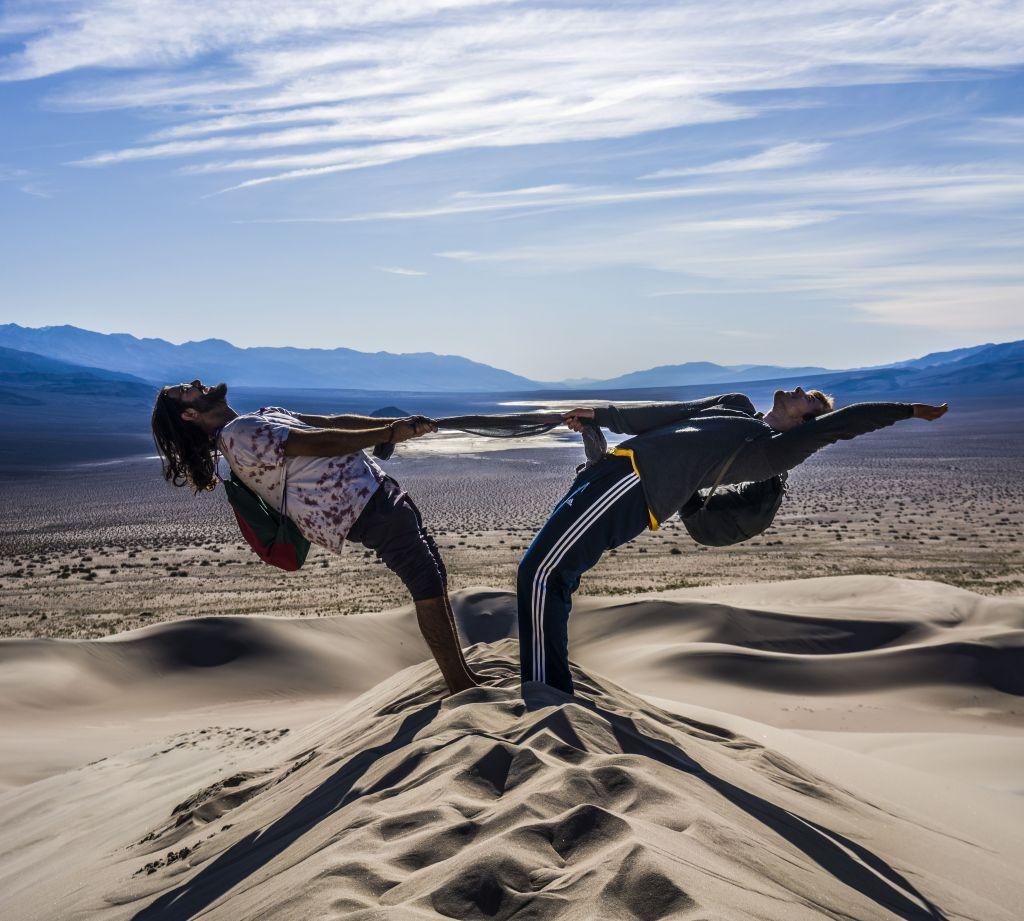 Zwei Jungs machen eine Balanceübung in der Wüste.