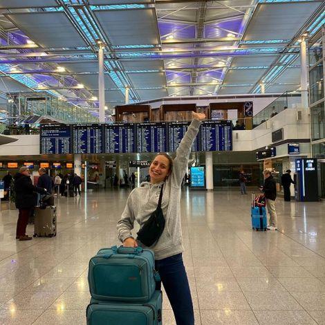 Ein Mädchen am Flughafen vor der Fliganzeige zusammen mit ihrem Koffer.