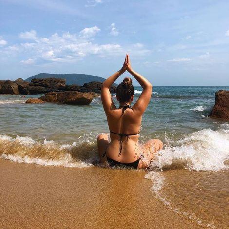 Mädchen sitzt am Strand und wird vom Wasser vom Meer nass gemacht