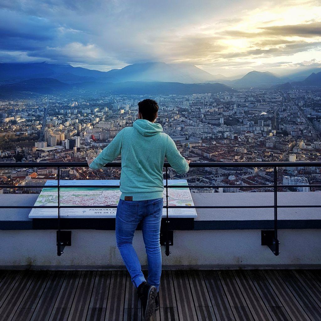zu sehen ist Tobi auf einer Aussichtsplattform, der Blick auf die Stadt Grenoble gerichtet.
