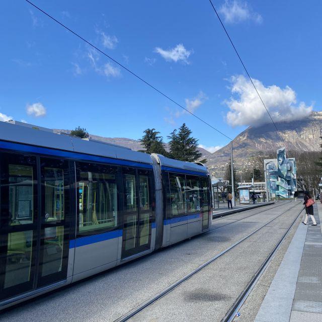 Man sieht eine Bahn und im Hintergrund den Berg Chartreuse.