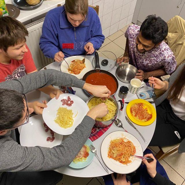 Vogelperspektive auf Tisch mit acht Studenten, die Spaghetti essen.