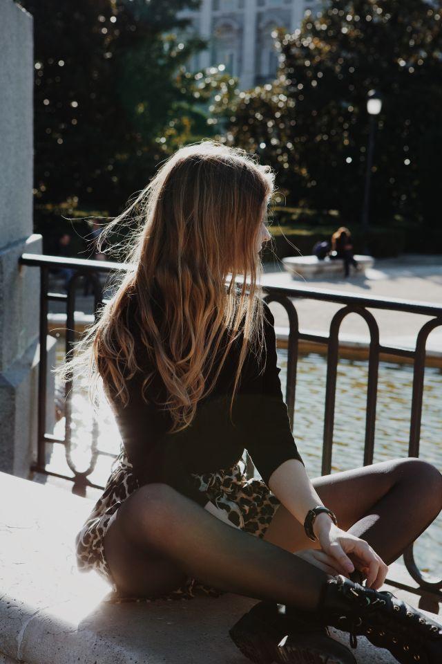 Studentin auf einer Bank vor dem königlichen Palast in Madrid