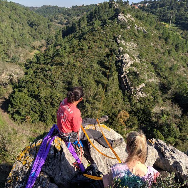 Eine Frau und ein Mann auf einem Felsen mit Blick auf einen grünen Hang.