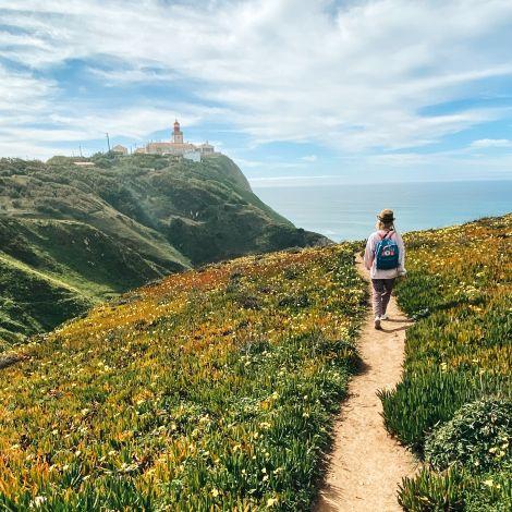 Frau auf kleinem Wanderweg, von gelben Blumen gesäumt mit Blick aufs Meer.