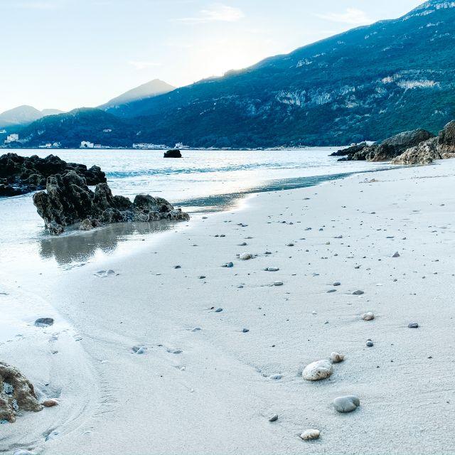 Strand mit Felsen und Blick aufs Wasser.