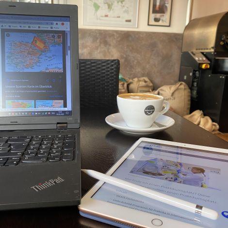 Ein Laptop, neben einem Tablet zusammen mit einer Tasse Kaffee