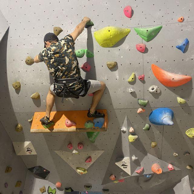 MAn sieht Tobi an einer Boulderwand.