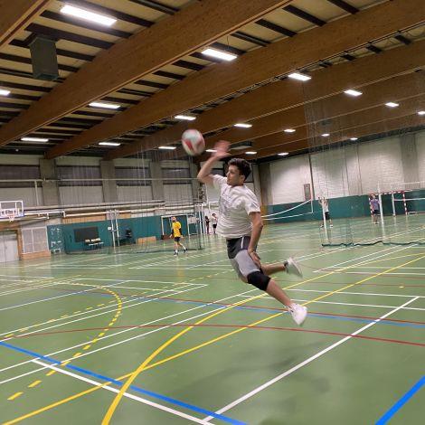 Man sieht Tobias, wie er einen Volleyball zurückschlägt.