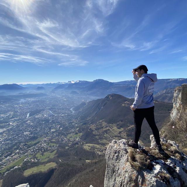 Man sieht Tobi auf einem Bergvorsprung posieren und im Hintergrund die Aussicht über Grenoble.