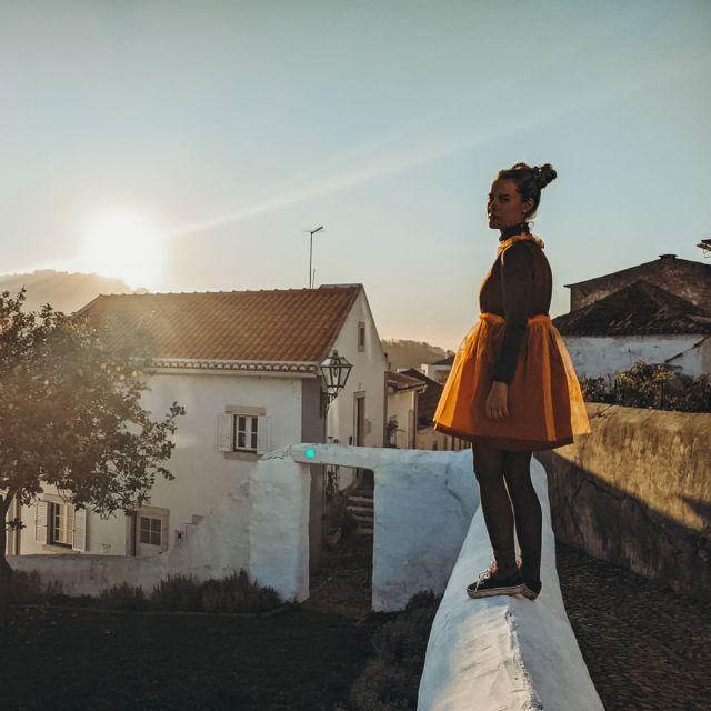 Frau steht auf einer weißen Mauer.