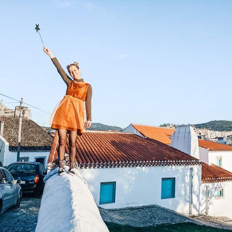 Frau steht auf einer Mauer mit Sternenstab in der Hand.
