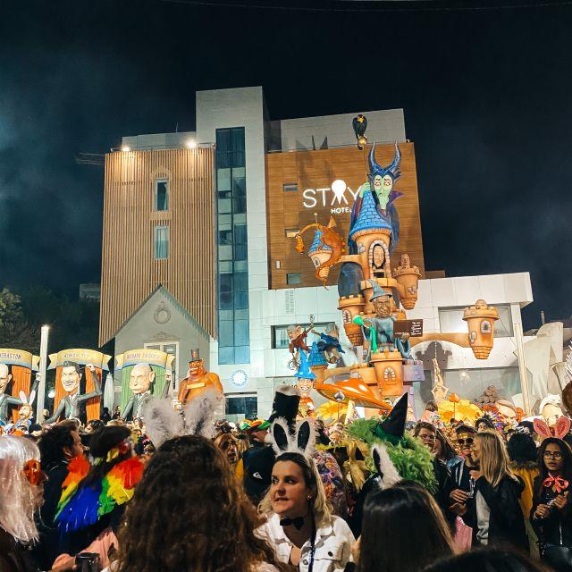 Menschenmenge vor Plastikschloss beim Karneval.