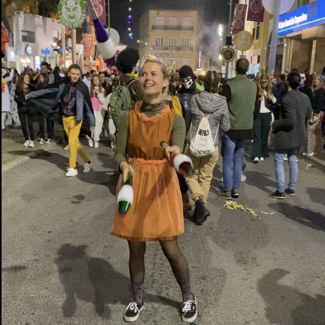 Frau mit Jonglierkeulen vor Menschen.