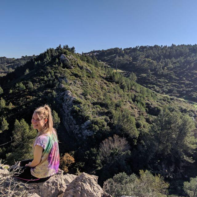 Frau auf Felsen mit Blick auf grüne Hügel.