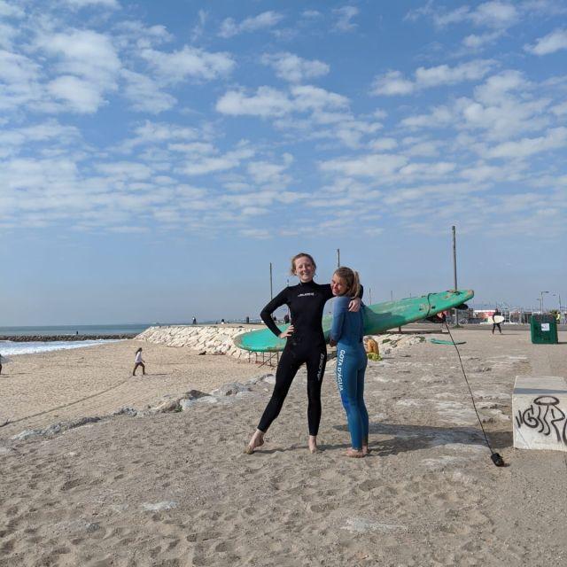 Zwei Surferinnen mit Surfboard am Strand.