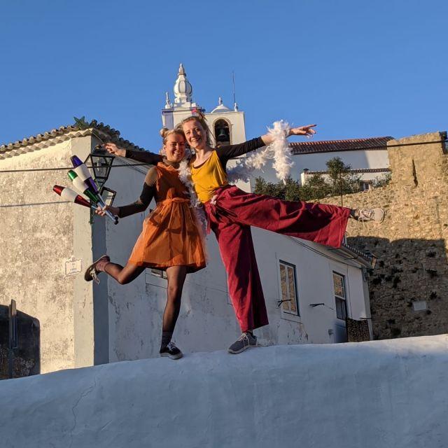Zwei Frauen stehen auf einer Mauer posen in bunten Kleidern.