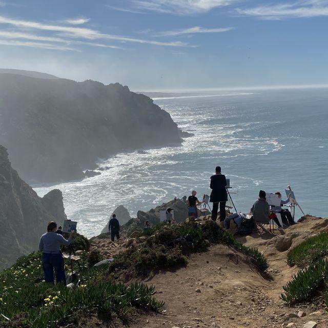 Maler mit Leinwand auf Kliff vor dem Meer.