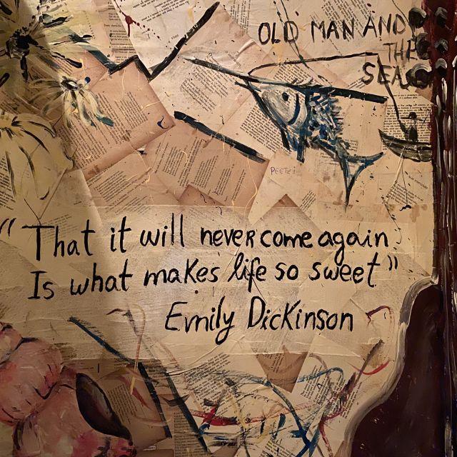 Wand mit Bücherseiten beklebt und Spruch im Vordergrund.