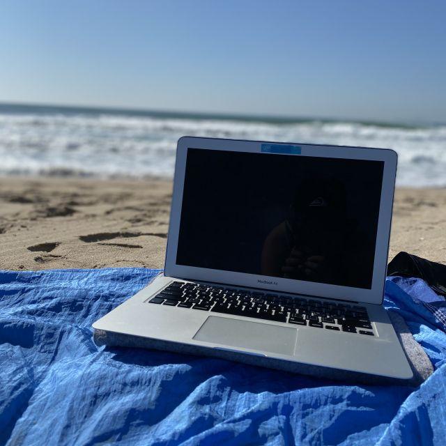 Laptop am Strand mit Meer im Hintergrund.