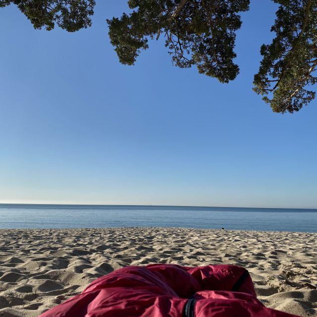 Schlafsack im Sand, im Hintergrund das Meer.