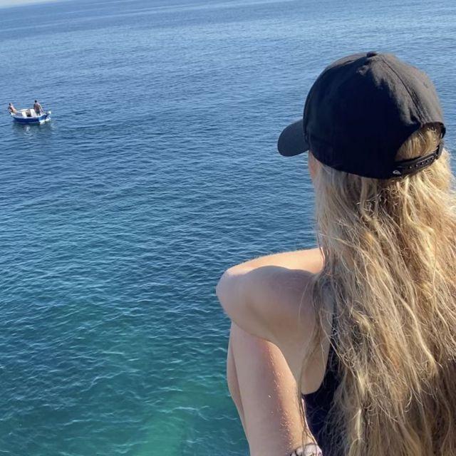 Rückenansicht einer Frau und im Hintergrund der Ozean.