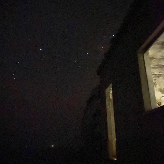 Sternenhimmel und die Silhouette eines Hauses im Vordergrund.