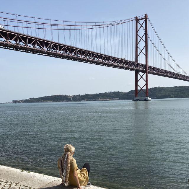Frau vor Hängebrücke über dem Tejo.