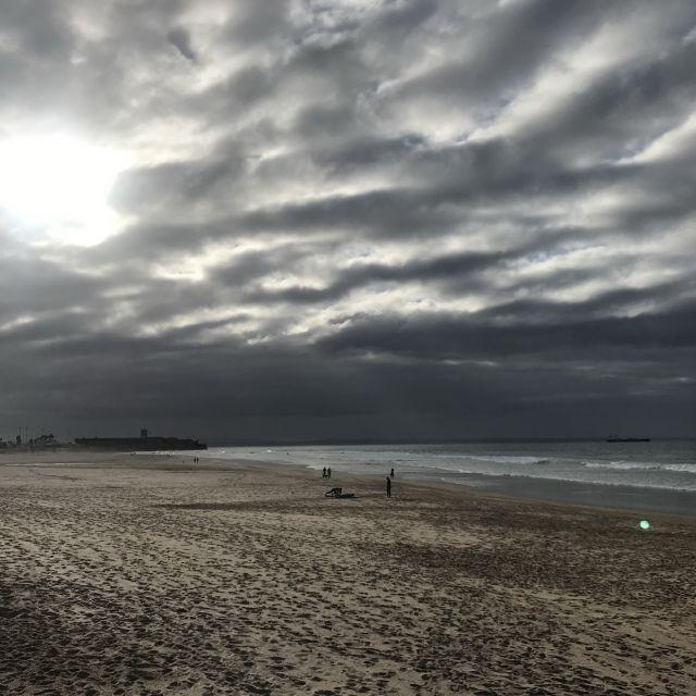 Strand mit dunklen Wolken und der Sonne, die durch die Wolken scheint.