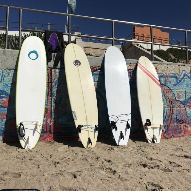 Vier Surfbretter am Strand angelehnt an einer Wand.