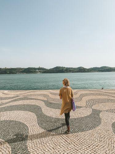 Frau läuft auf großem Platz. Im Hintergrund der Tejo.