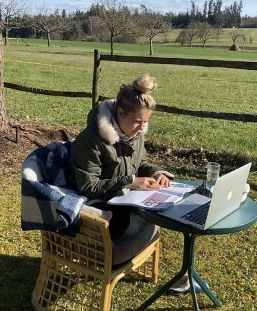Frau sitzt an einem kleinen Tisch im Garten mit Laptop und Buch.
