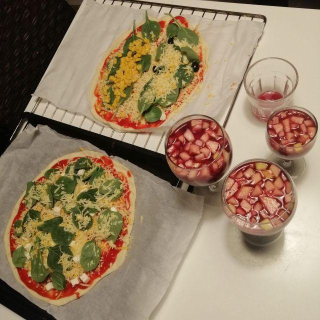 Zwei selbstgemachte Pizzen und drei Gläser, die gefüllt sind mit Sangria