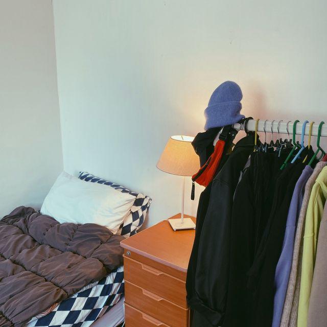 Zimmer mit Bett, Kleiderstange und Nachttisch