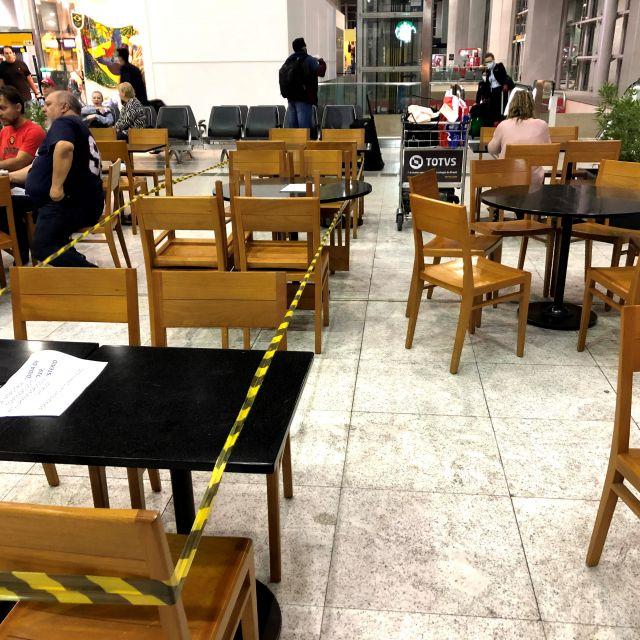 Eine Tischreihe ist mit Absperrband gesperrt und schafft somit Abstand im Restaurant.