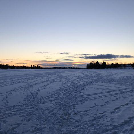 Fußspuren und Langläufer im Schnee auf gefrorenem Fluss