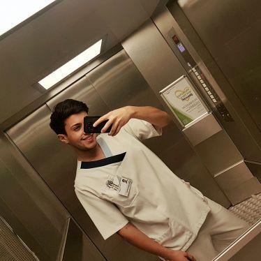 Man sieht Tobi in Krankenpflegeuniform in einem Aufzug, wie er ein Selfie macht.