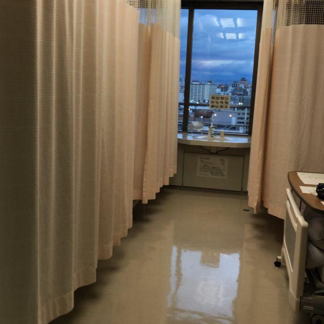 Man sieht in ein Patientenzimmer mit vier Betten (je zwei rechts und links), welche durch Vorhänge voneinander getrennt werden können. Drei Vorhäge sind zu.