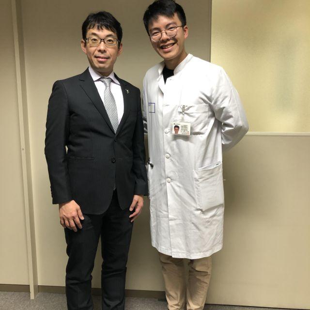 Links steht ein japanischer Mann mittleren Alters im Anzug und rechts stehe ich im weißen Kittel.