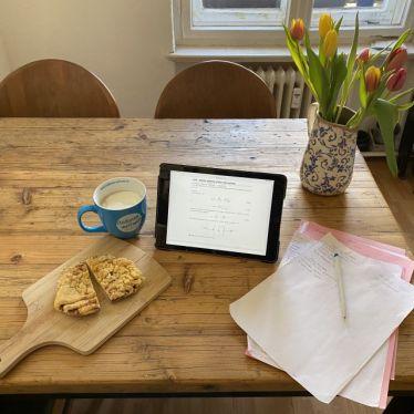 Tisch mit Lernsachen und Tablet. Außerdem eine Tasse mit Kaffee und ein Strauß Tulpen