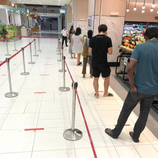 Schlange im Supermarkt mit 1m Abstand voneinander