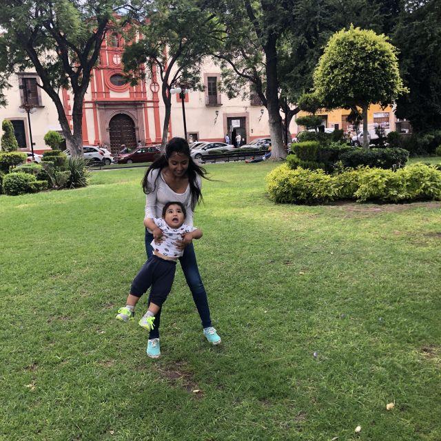 Kleinkind in den Armen der Mutter im Park