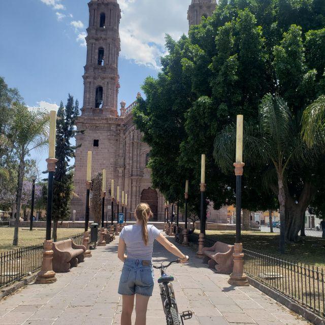 Frau mit Fahrrad steht vor einer Kirche