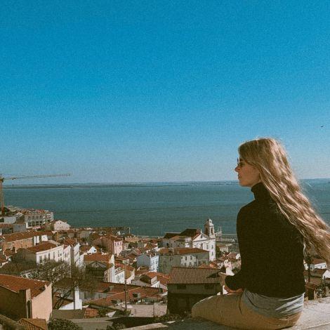 Rückenansicht von einer Frau, die auf einer Mauer mit Blick über Lissabon sitzt.