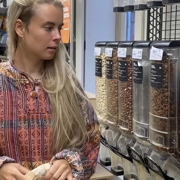 Frau im Supermarkt vor Nussbehältern.