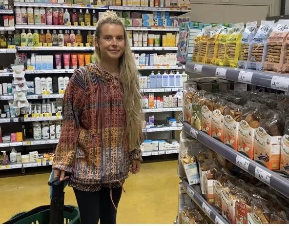 Frau im Supermarkt vor Obstsäften.