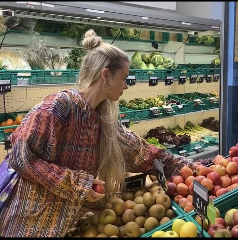 Frau im Supermarkt vor Obstkisten.